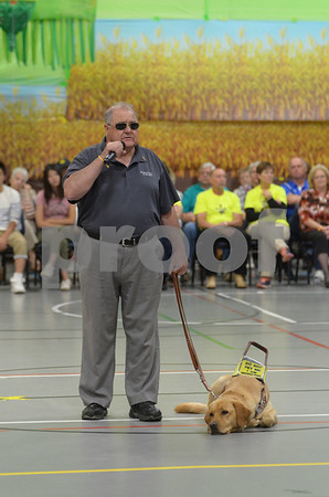 -Messenger photo by Jesse Major<br /> Len Quinn, of Green Lake Wisconsin, stands with his Leader Dog, Slyder, as he tells inmates at Fort Dodge Correctional Facilty that they are heroes for raising Leader Dogs.