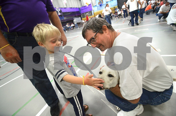 -Messenger photo by Jesse Major<br /> Four-year-old Brent Thielen, of Glidden, pets 13-month-old Gabby, a Leader Dog who was trained by Fort Dodge Correctional Facility inmate John Cowles, right.