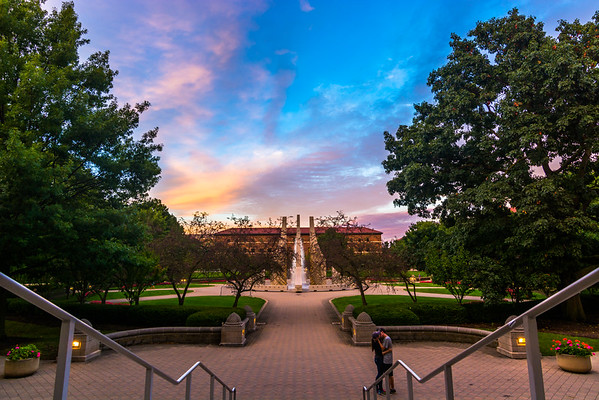 """Man, it has been quite the week. Applying for jobs can be quite stressful, but you have to go out and take some photos.   I was sitting on top of HOVD Hall trying to get some interesting perspectives on the fountain, when this couple walked up and started """"talking."""" I don't know if they knew I was there, but I think having them in this photo, completes the frame.   Also, for those who want to see more photos, I have been working on a website. The current link is in the bio. Feel free to take a look and let me know your thoughts.  #Nikon #Landscape #Purdue #Engineering #Sunset #Love"""