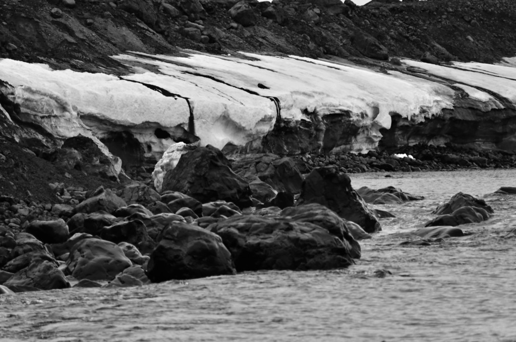 Solifluction: melting mud from permafrost layers flows over snow patches into the sea, Cape Flora, Franz Josef Land