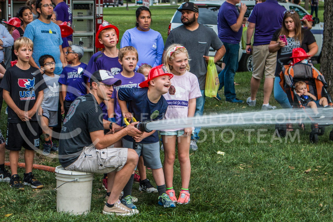 Manhattan locals celebrate during Purple Power Play 2017 in Manhattan, Kan. on September 1, 2017. The Purple Power Play festival celebrates the beginning of the 2017 K-State football season. (Logan Wassall | Collegian Media Group)