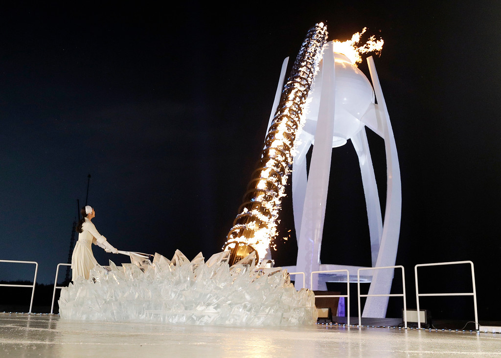 . A torchbearer lights the Olympic flame during the opening ceremony of the 2018 Winter Olympics in Pyeongchang, South Korea, Friday, Feb. 9, 2018. (AP Photo/David J. Phillip,Pool)