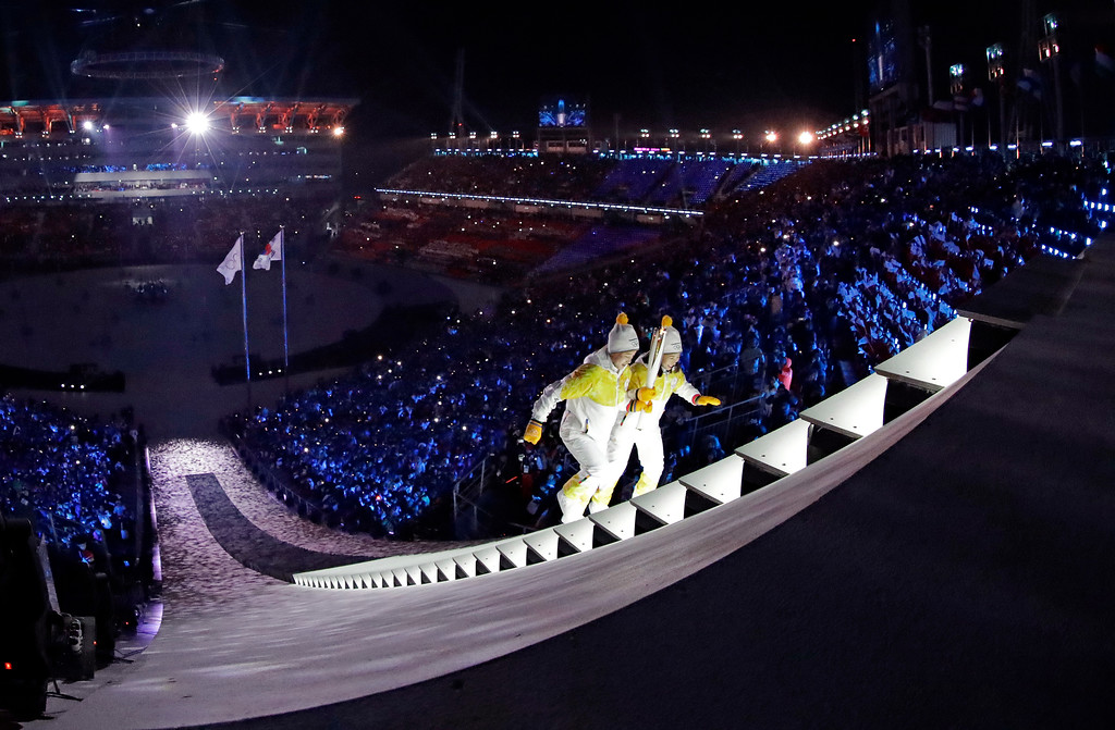 . North Korea\'s Jong Su Hyon, left, and South Korea\'s Park Jong-ah carry the torch during the opening ceremony of the 2018 Winter Olympics in Pyeongchang, South Korea, Friday, Feb. 9, 2018. (AP Photo/David J. Phillip,Pool)