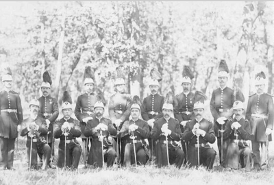 """Knights of Pythias, Uniformed Ranks Lodge Group Photo  This sword is a representative example of a Knights of Pythias society or lodge sword. The Order of Knights of Pythias """"is a great international fraternity which was founded in Washington, DC, February 19, 1864 by Justus H. Rathbone..."""" The """"Fraternal Order of Knights of Pythias and its members are dedicated to the cause of universal peace.""""  The most distinctive feature on this sword is the """"Knight's Head"""" pommel with a lion patiently resting on - or guarding - the crest. A chain is usually found as a knuckle-guard running from the knight's visor to a phoenix bird on the cross-guard finial (both finials are in the likeness of a phoenix bird). Also, the clamshell on the obverse cross-guard is very distinctive in shape in that it is not a true oval but very near a true clamshell. The clamshell may also display the letters """"UR"""" (Uniformed Ranks) which was a militant faction of the Knights of Pythias, now disbanded (believed in the 1950s). On the reverse of the cross-guard is usually found the letters """"FCB"""" (Friendship, Charity, Benevolence).The hilts are cast from a variety of metals but usually the grips are of brown or black leather, wrapped in ornamental brass wire or cord. They are very ornate in appearance and were not intended for combat. Fraternal, Lodge, or Society swords are relatively inexpensive to own and are fun to collect. There are seemingly infinite variations and I have owned many. Most are marked - usually Lilley, Ames, or Pettibone - and are found in infinite degrees of condition. This particular specimen is from the 1890s.    http://arms2armor.com/Swords/pythias1.htm"""