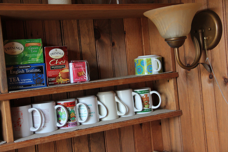 A shelf with cups in the coffee area next to the meetinghouse.