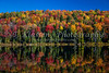 Colorful fall foliage reflected in the calm water of a lake in La Mauricie National Park, Quebec, Canada.