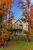 A home with fall foliage color in the forest near Magog, Eastern Townships, Quebec, Canada.