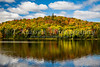 Brilliant fall foliage color in the mountains reflected in the lake of Mont-Tremblant National Park, Quebec, Canada.