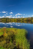 The calm water of the Sainte Maurice River reflecting colorful fall foliage in shawinigan, Quebec, Canada.