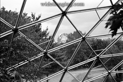 Geodesic dome structure formerly the World's Fair Churchill pavilion relocated serving as a netted aviary, from October 1989. Unisphere appears in background.