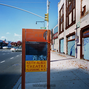 Landmark Status sign in front of the RKO Keith's(Albee) Theatre, looking West down Northern Blvd. at the intersection of Main Street. The Serval Zipper clock tower appears in the background left.