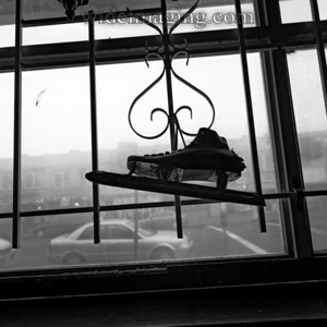 Ancient speed skate overlooks Jamacia Avenue in the Klingbeil Shoe Lab window, from October 2004.