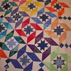 This pattern emerges by framing the small block by triangles (a square in a square) and using an alternate pinwheel block.