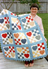 1987 Bare foot quilter, Pat, holds nine patch and hearts baby quilt in Houston, Texas.