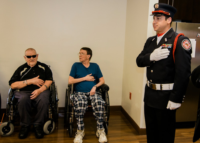 Fitchburg Firefighter and USMC veteran Anthony Liberatore stands for the Pledge of Allegience during the Quilts of Valor ceremony at the Golden Living Center on Friday afternoon. SENTINEL & ENTERPRISE / Ashley Green
