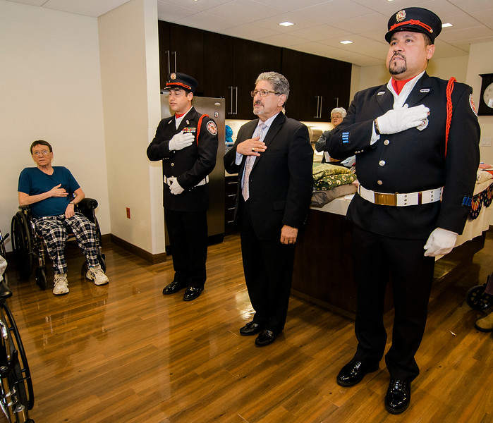 Fitchburg Firefighters Anthony Liberatore and Michael Torres, along with Mayor Stephen DiNatale (center) stand for the Pledge of Allegience during the Quilts of Valor ceremony at the Golden Living Center on Friday afternoon. SENTINEL & ENTERPRISE / Ashley Green