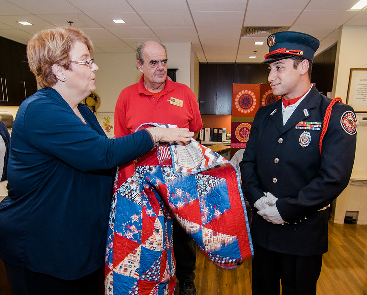 Darlene Coit and Lee Crocker present Fitchburg Firefighter and USMC veteran Anthony Liberatore with a Quilt of Valor during a small ceremony at the Golden Living Center on Friday afternoon. SENTINEL & ENTERPRISE / Ashley Green