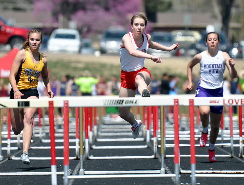 Loveland's Hannah Weinmaster, middle, races to the finish in the 100-meter hurdles as Thompson Valley's Kara McKee, left, and Mountain View's Lauren Steege chase Thursday April 13, 2017 at the R2J Invite in Loveland. (Cris Tiller / Loveland Reporter-Herald)