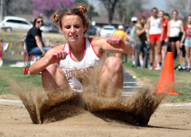 Loveland's Blair Bernhardt splashes the sand during the long jump Thursday April 13, 2017 at the R2J Invite in Loveland. (Cris Tiller / Loveland Reporter-Herald)