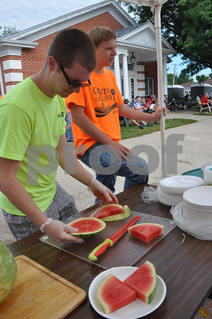 -Messenger photo by Joe Sutter<br /> <br /> Steven Oswald, left, and Ethan Lenz slice watermelons at the Manson Mennonite Church booth during RAGBRAI Monday.