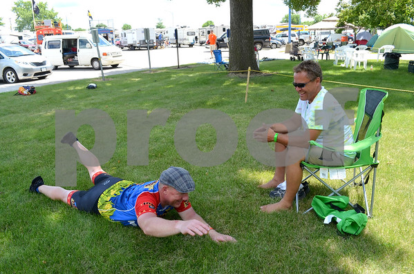 - Messenger photo by Peter Kaspari<br /> <br /> Tim Burmeister, left, of Milwaukee, Wisconsin, stretches out after arriving in Fort Dodge during RAGBRAI. His support driver, Dan Romberg, left, shares a laugh.