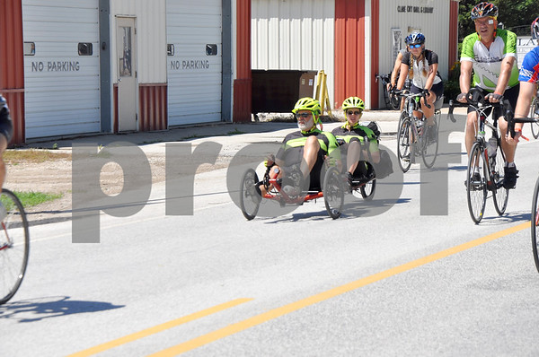-Messenger photo by Joe Sutter<br /> <br /> Recumbents, trikes, and tandem bikes can be seen on the RAGBRAI route—sometimes all at once. Bill and Sandy Barry, of Grand Rapids Michigan, ride through Clare Monday afternoon on a recumbent tandem tricycle.