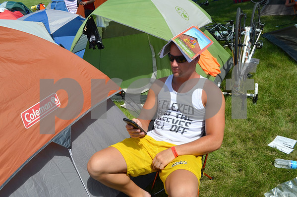 - Messenger photo by Peter Kaspari<br /> <br /> Brian Holt, of Altoona, uses a magazine as shade after setting up his tent during RAGBRAI at the Fort Dodge Senior High fields Monday. Though a unique way of getting shade, Holt admitted it wasn't very effective.