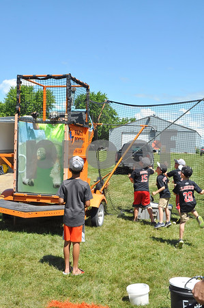 -Messenger photo by Joe Sutter<br /> <br /> RAGBRAI rider Jim Fox, of Houston, Texas, cools off at the Northwest Iowa Badgers team dunk tank in Clare Monday. After throwing the baseball several times and missing, the team decided to all rush forward at once and hit it manually.