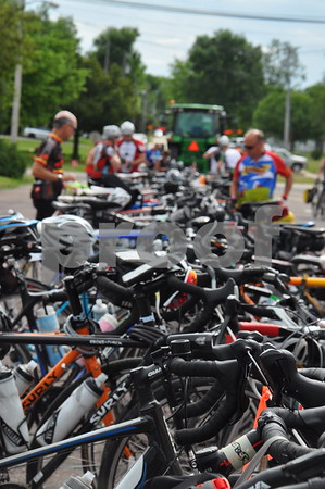 -Messenger photo by Joe Sutter<br /> <br />  A cable stretched between two tractors serves as a bike rack for RAGBRAI in Manson Monday.