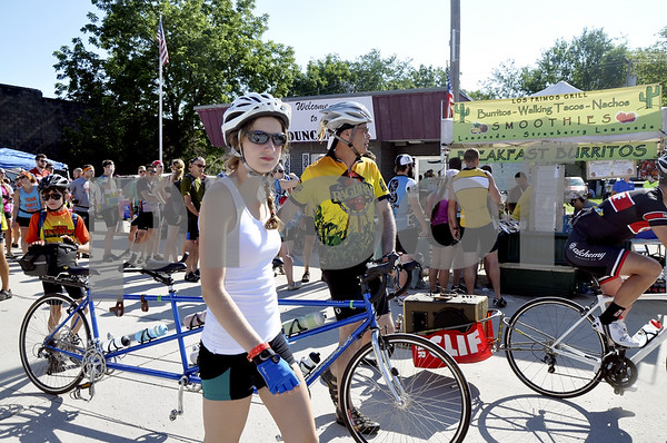 - Messenger photo by Peter Kaspari<br /> <br /> Agathe Vanderbroucke, 16, left of Paris, France, walks alongside a multi-seat tandem bike with Steven Lawyer, of New Virginia. Lawyer said Vanderbroucke is the daughter of a longtime friend of his from Paris and invited her on RAGBRAI this year. The bike ride stopped in Duncombe Tuesday. Lawyer's son, Sam Lawyer, 12, is at the back of the bike.