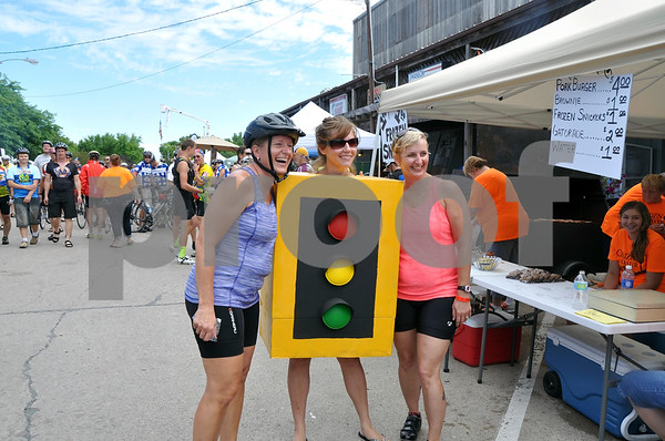 -Messenger photo by Joe Sutter<br /> <br /> RAGBRAI riders Lisa Lott, Ottomwa, and Jill Klepper, Spring Valley Minnesota, pose with Annette Westering in Manson Monday, Westering was there to represent the only stoplight in Calhoun County, located in downtown Manson, and provide photo ops for the riders.