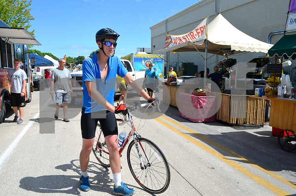 - Messenger photo by Peter Kaspari<br /> <br /> Devin Lux, of Cherokee, walks his bike through the vendor area during RAGBRAI Monday. Fort Dodge was an overnight stop on the route.