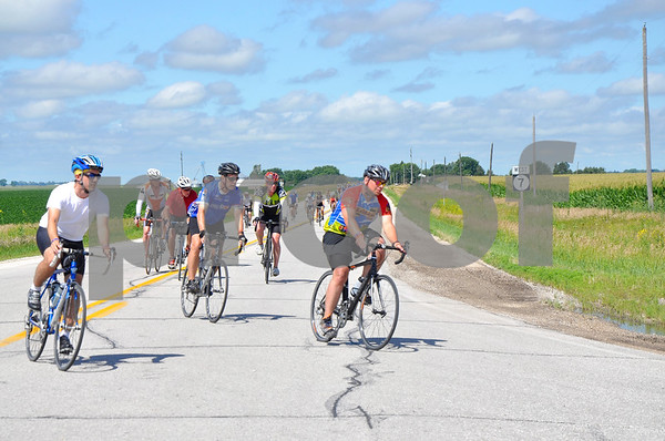 -Messenger photo by Joe Sutter<br /> <br /> RAGBRAI riders round the corner of Iowa Highway 7 and Calhoun County Highway P19 on their way from Manson to Clare Monday morning.