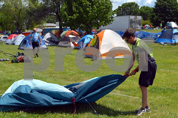 - Messenger photo by Peter Kaspari<br /> <br /> John James, of Augusta, Maine, sets up his tent in the field at Fort Dodge Senior High School Monday.