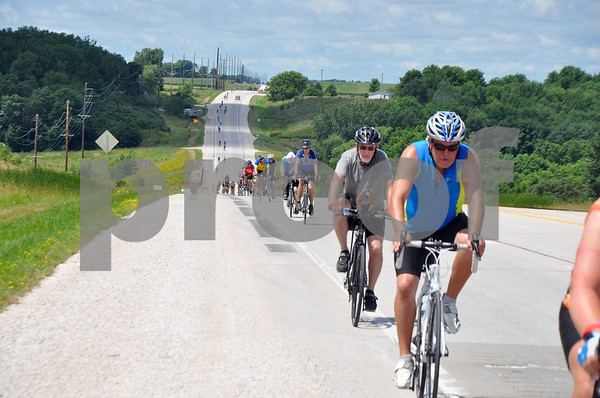 -Messenger photo by Joe Sutter<br /> <br /> RAGBRAI riders make their way up the hill on Iowa Highway 7 on their way into Fort Dodge Monday afternoon.