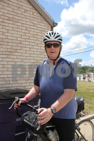 Neil Meyer paused briefly for a photo on his way to the RAGBRAI camp site. He was on of thousands of RAGBRAI riders that stayed in Fort Dodge overnight  when  they rolled through  town on Monday, July 20, 2015.