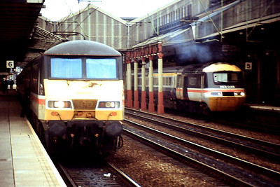 With an unidentified Class 90 in the foreground, HST set 253 045 is seen at Crewe. 1989.