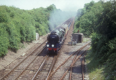 "WC Class Bulleid Pacific 34027 ""Taw Valley"" (masquerading for a few hours as 34026 ""Yes Tor"") passes West Dean sidings as it heads towards Salisbury with a special from Eastleigh on 28th June 1992."