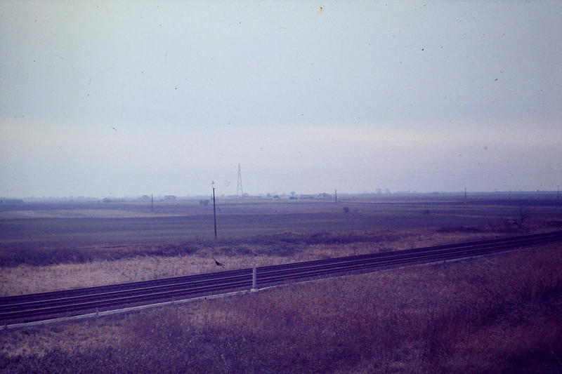 'The Fens with John & Avril's farm in mid distance, 1975'. Brian certainly had an eye for landscapes! Taken from the top of the Up Hump Reception Sidings looking across the GN/GE mainline. Note to potential tourists: we've got a lot more just like this!