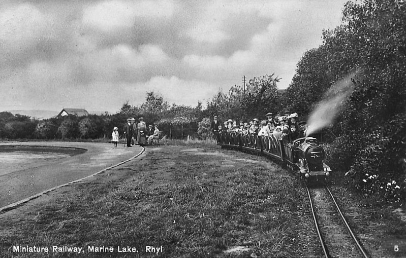 RHYL MINIATURE RAILWAY - The Rhyl Miniature Railway is a 381 mm gauge railway line that runs in a circle around a boating lake near the promenade, to the west of the town centre. The line opened in 1911 and closed in 1969, when the track was removed. The line was relaid in 1978 and the railway is now operated by Rhyl Steam Preservation Trust. The railway has a long association with one type of locomotive, a class of  4-4-2 tender engines built by Albert Barnes & Co of Rhyl. Here we see one of the Atlantics hauling well loaded train in the 1920's - card posted in September 1931.