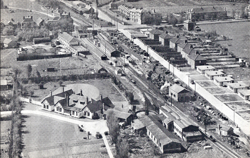 NEW ROMNEY STATION - Seen here from the air looking west, locoshed in the foreground, station beyond, probably just postwar (note prefabs to the right). The standard gauge station of New Romney and Littlestone-on-Sea can be seen top centre, beyond the roadbridge, with the goods yard running down behind the RH&DR station. This branch was closed in March 1967 and was latterly worked by 'Thumper' DEMU's.