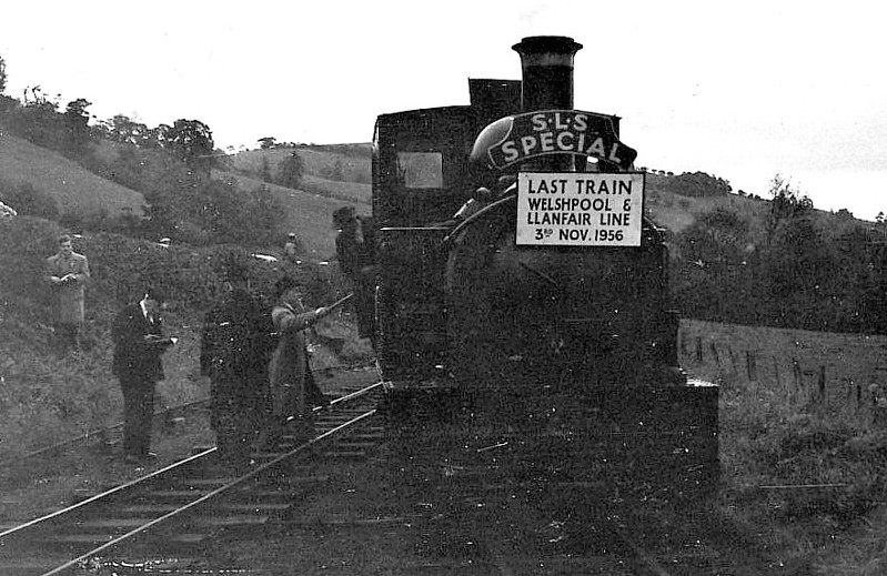 WELSHPOOL & LLANFAIR LIGHT RAILWAY - SLS 'LAST DAY SPECIAL' - The Railway officially closed on November 5th, 1956, and the SLS organised a special train on November 3rd. As the line had closed to passengers 25 years previously, there was no passenger stock available and everyone had to crowd into open wagons - here we see No.822 THE EARL running round I think at the end of the outward leg - note the added headboard - what is that man doing with that stick?