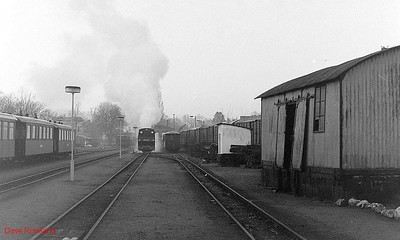 A view of the yard at Putbus, taken from outside of the locomotive shed; the station is to the left of the coaches, and 2-8-0T 99 4802 has started to return to attach to its train, which will form the 06.40 passenger service to Göhren, on the seaside holiday resort island of Rugen. 10th April 1991.