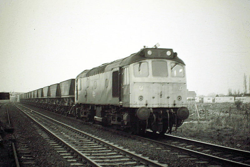 25323 has run round in Whitemoor and waited for a new path as it heads west with 6E07 Foxton - Thoresby Coal Empties, 21/03/85. The loco was withdrawn in March 1987.