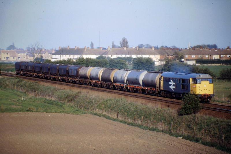 31142 approaches the A141 bridge on 6N84 Duxford - Tees Yard, 25/04/88.