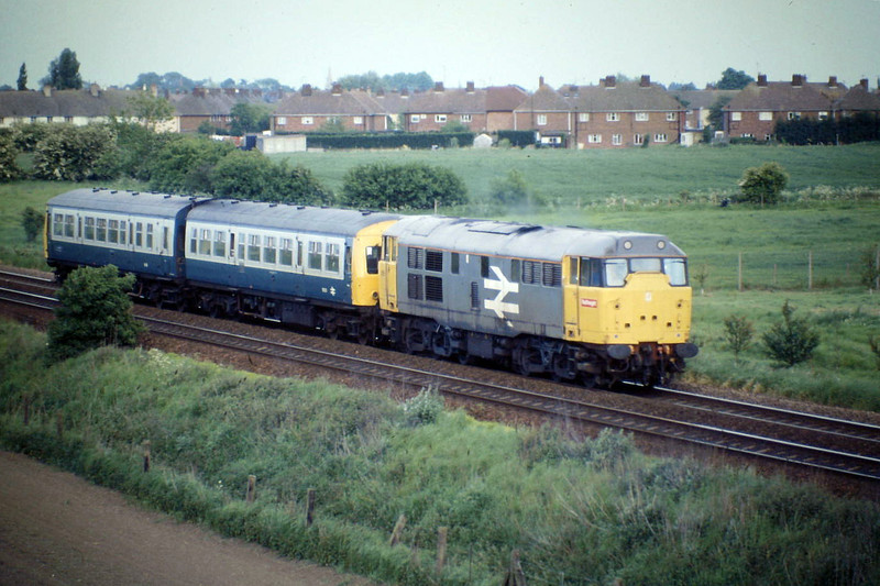 31155 heads towards Peterborough near the A141 Bridge with a Class 101 DMU in tow, 25/05/88.