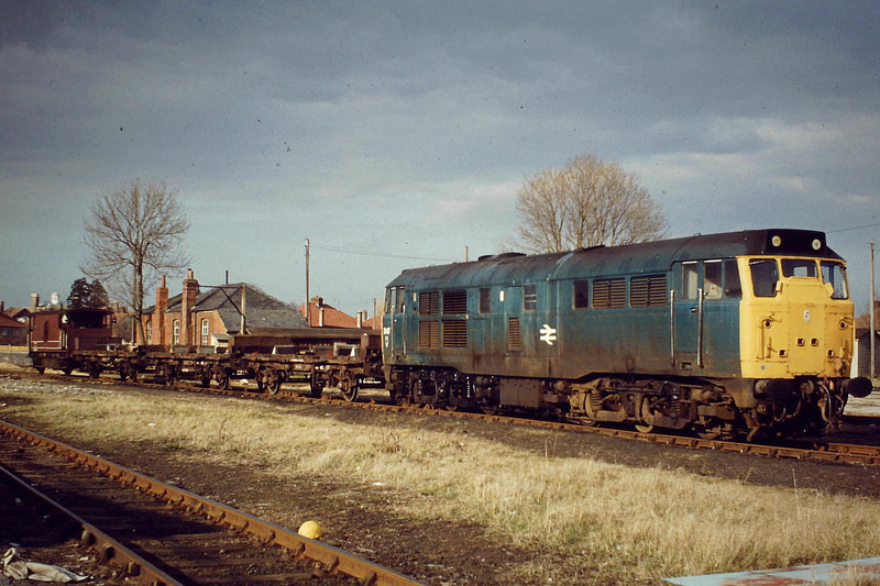 31417 waits to return to Whitemoor with a short rake of steel empties, Wisbech Yard, 03/82. Note LMS type brakevan. Also, the Goods Offices still standing on the Dock - this used to be Wisbech East's Goods Yard at one time. I think this is one of my favourite pictures of mine.