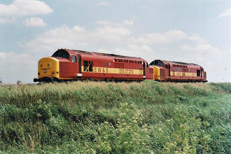 37370 and 37667 head west past Horsemoor, 24/06/98. 37370 was withdrawn in 11/00 whilst 37667 was withdrawn in 07/06 and sold to DRS, where it is part of the present fleet.