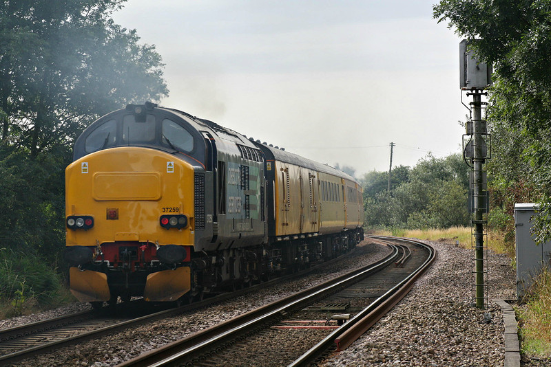37259 brings up the rear of 1Q48 Derby RTC - Norwich test train as it passes Badgeney Road LC, 13/08/12, lead by 37603. This loco started life as D6959 in 01/65, became 37 259 in 03/74, was fitted with self-steering bogies as 37380 in 06/88, reverting to 37259 in 09/02 when sold to DRS, it's current operators.
