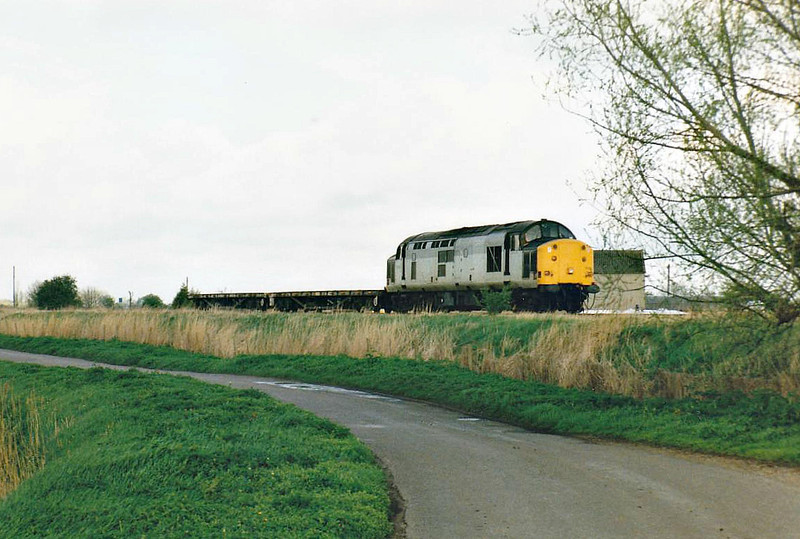 37509 heads east past Horsemoor on a sort rake of rail flats, 06/04/98. This engine was withdrawn in 12/01.